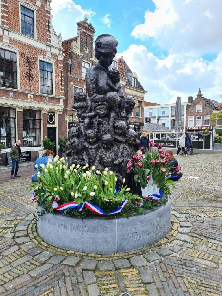 Het beeld van Truus Wijsmuller omringd door tulpen. De rood-witte is de Tante Truustulp.