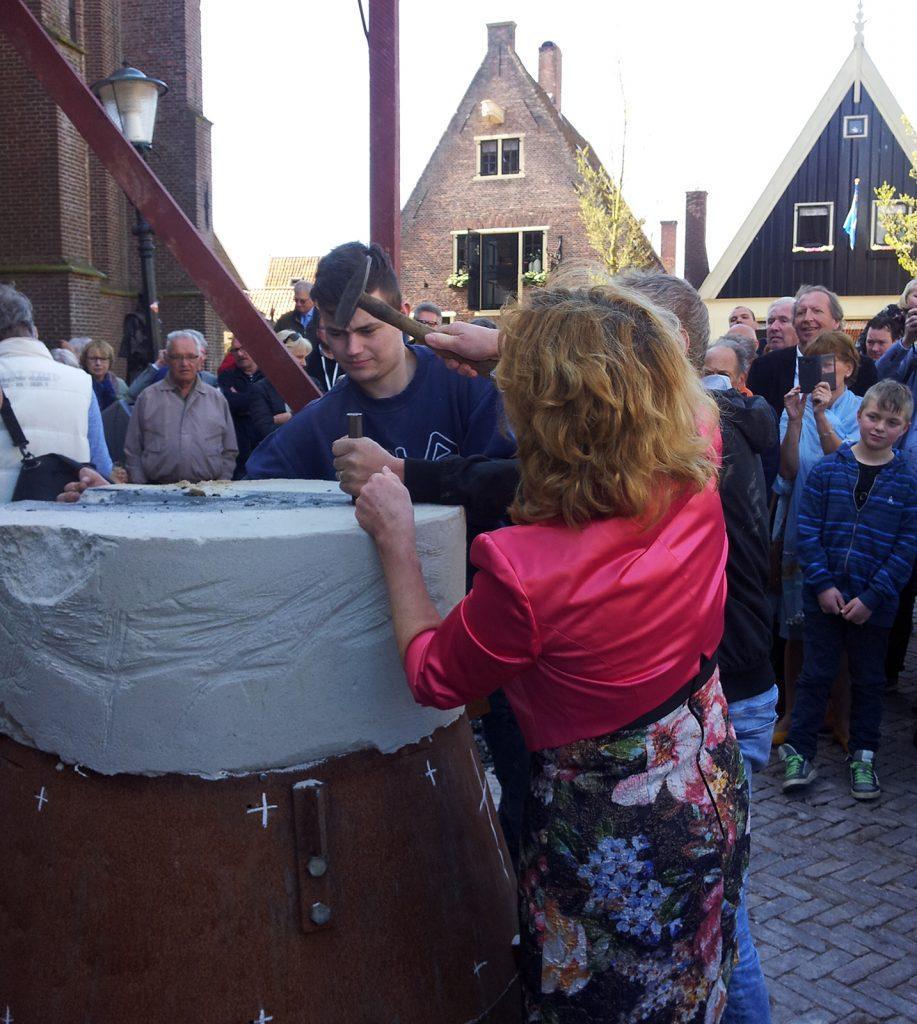 Wethouder Anjo van de Ven onthult de zojuist gegoten klok. Naar een oud gebruik had zij van tevoren in de smeltkroes een messing 'geluksmunt' geworpen.