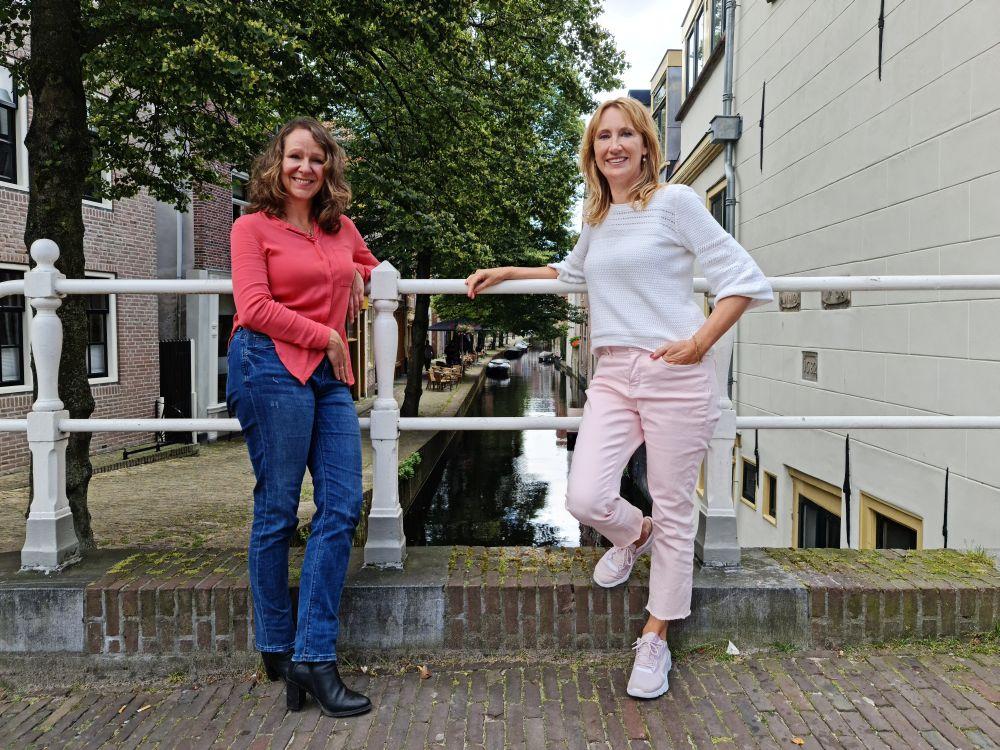 """Nancy de Jong en Simone van der Vlugt met uitzicht op de Kooltuin, een dertiende-eeuws stukje Alkmaar. Simone: """"Hier laat ik ook mijn personages langs komen met hun voertuig"""